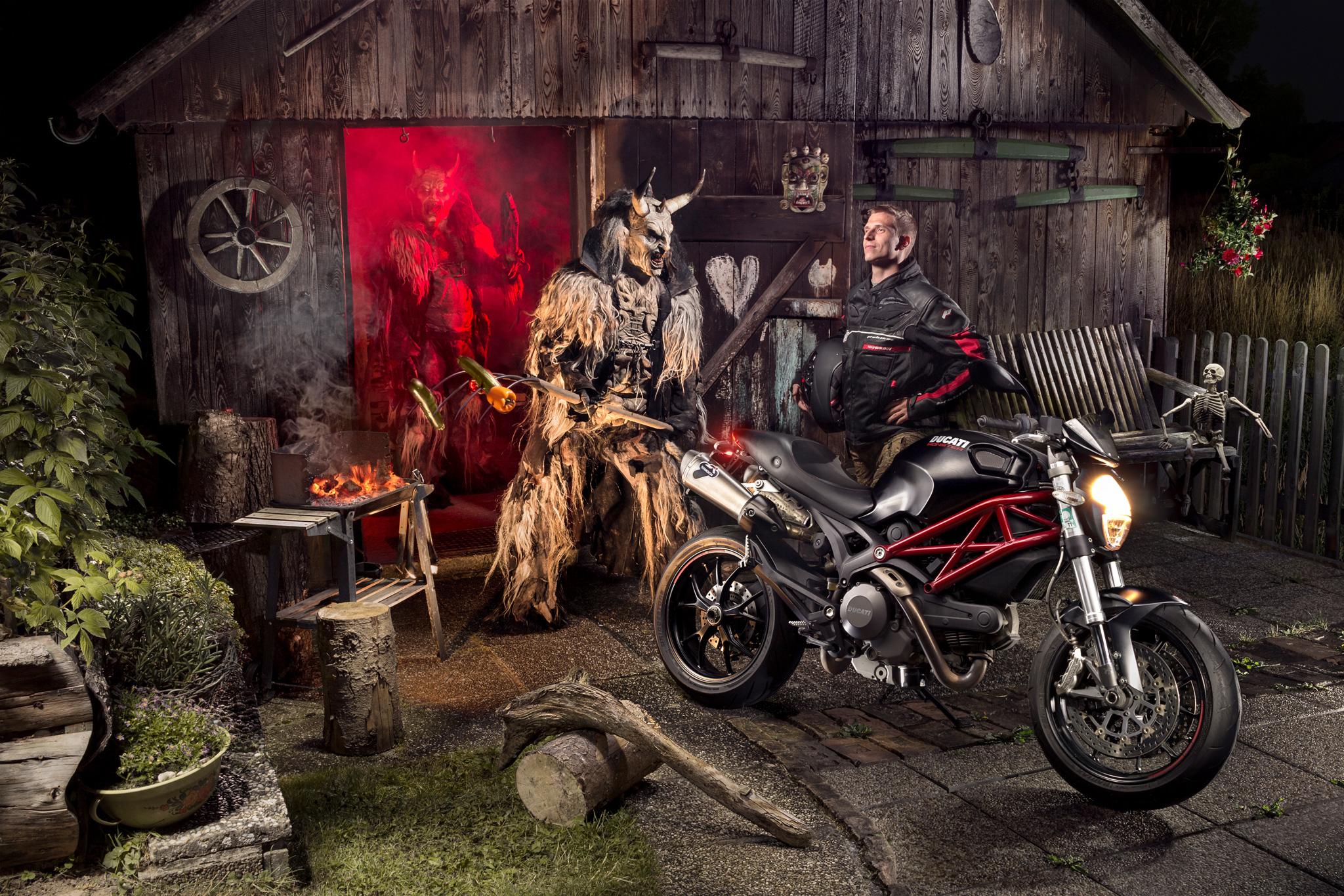 Motorrad und Perchten Monster vor Holzhütte mit Griller, Skelett und Blumenbeet Motorrad Fotografie Biker