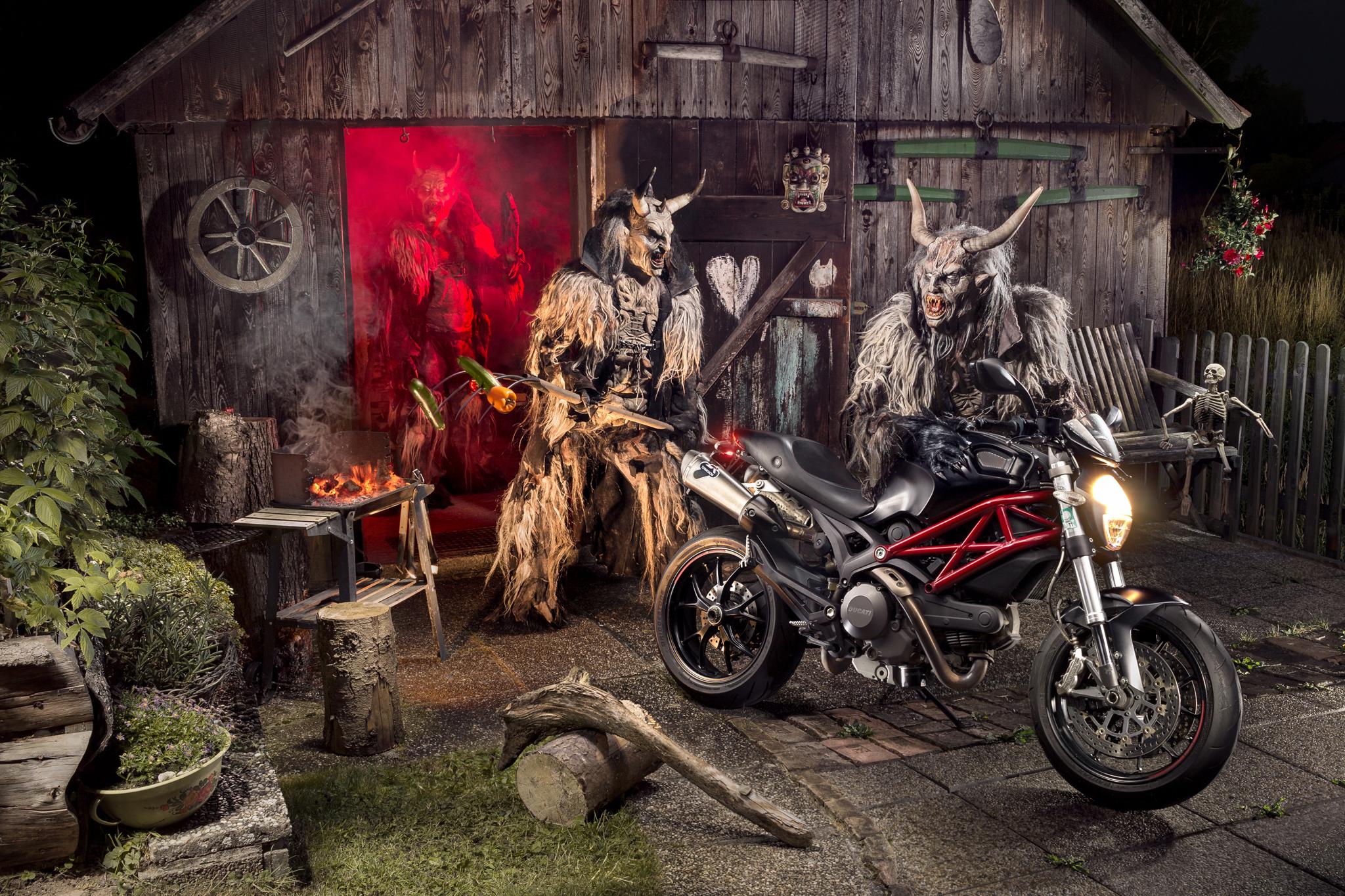 Motorrad und Perchten Monster vor Holzhütte mit Griller, Skelett und Blumenbeet Motorrad Fotografie