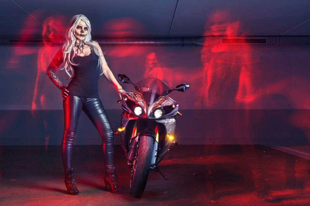 Frau mit Halloween Make Up und Motorrad in der Garage mit Geistern